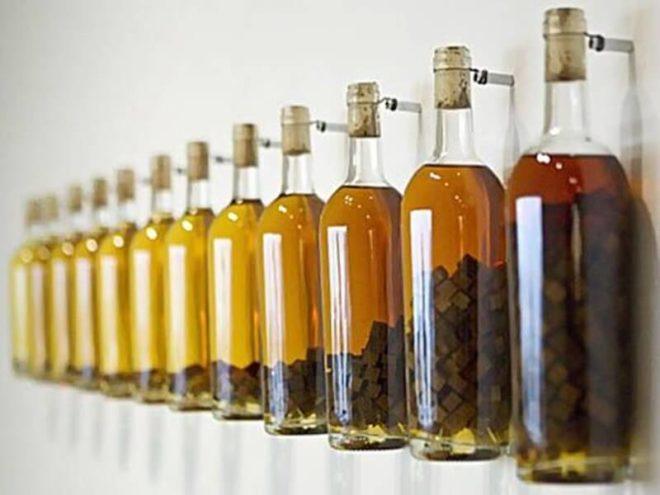 бутылки в ряд с самогоном и дубовыми кубиками
