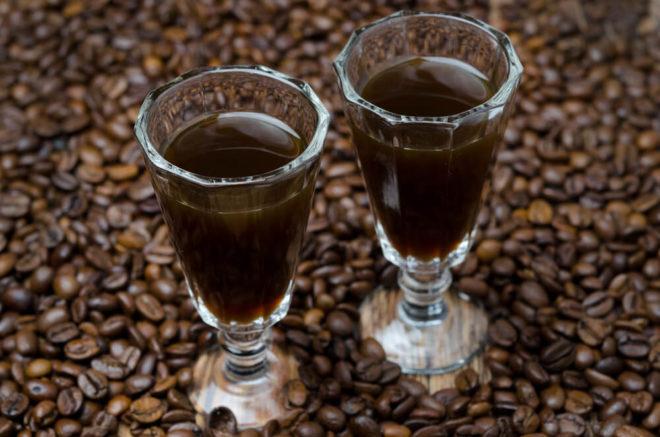 две рюмки с темной настойкой и кофейные зерна